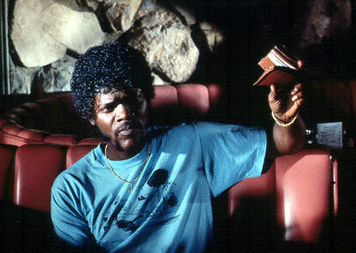 Samuel Jackson sitting on couch with a book in his hand