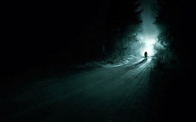 A man standing alone on the dark forest road