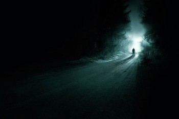 Deserted road during the night with a man-silhouette on its end