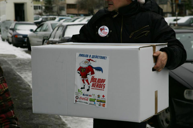 man holding big holiday heroes charity box