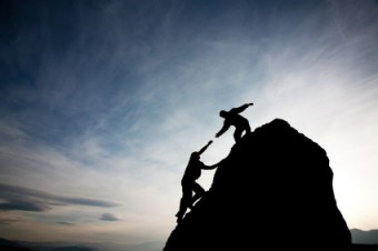 One man helping another to climb a rock