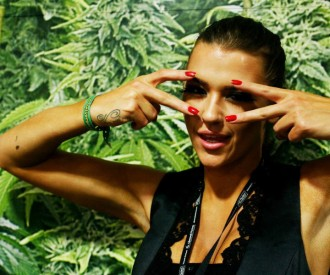Beautiful woman in front of marijuana plants