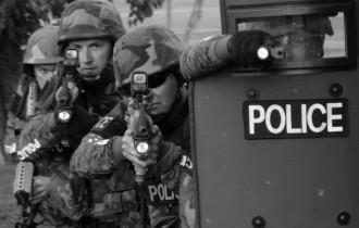 SWAT raiding team behind a shield