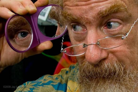 A beard man holding small mirror